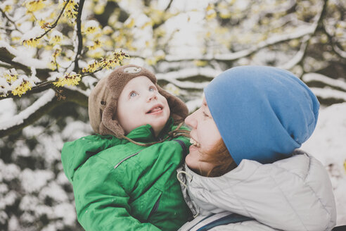 Portrait of little boy enjoying his first snow on his mother's arms - IHF00078