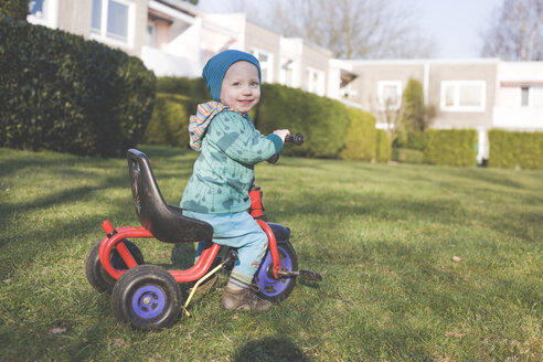 Portrait of happy little boy with tricycle on lawn - IHF00087