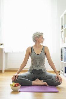 Woman practising yoga at home, having a healthy fruit snack - FBAF00678