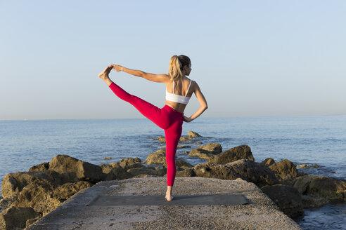 Young woman practicing yoga on the beach, doing standing balance, Utthita Hasta Padangustasana - JPTF00101