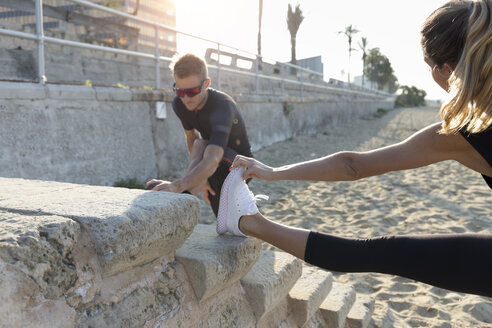 Sporty couple warming up for training on the beach - JPTF00110