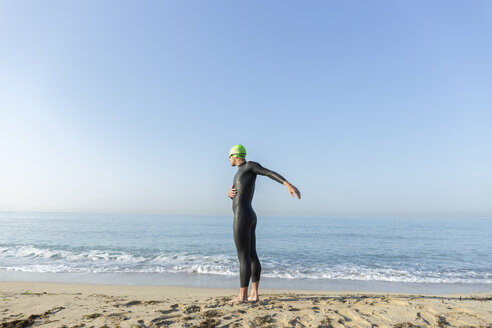 Triathlete warming up before swimming in the ocean - JPTF00116