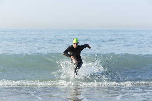 Triathlete in wetsuit running out of the sea - JPTF00119