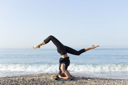 Young woman practicing yoga on the beach, doing headstand - JPTF00125