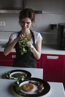 Smiling young woman garnishing plates of vegetarian food in her kitchen - LJF00087