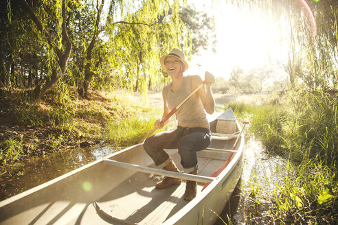 Caucasian woman rowing canoe in rural creek - BLEF05809