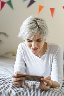 Smiling woman using cell phone on bed at home - FBAF00690