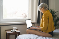 Woman sitting on bed at home using laptop - FBAF00696