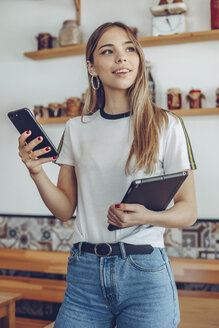 Portrait of young woman holding a tablet in a cafe - ACPF00520