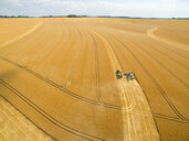 Aerial landscape view of combine harvester and tractor trailer in sunny golden barley field - JUIF01155