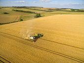 Aerial landscape view of combine harvester filling tractor trailer in sunny golden barley field - JUIF01158