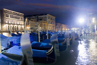 Streetlight shining over covered moored gondolas along architectural buildings in the Grand Canal at night, Venice, Italy - JUIF01164