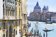 Gondolas and boats in sunny Grand Canal in front of Santa Maria della Salute and architectural buildings in Venice, Italy - JUIF01173