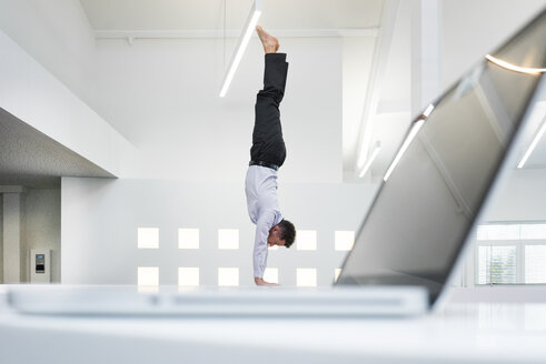 Businessman doing a handstand at laptop in office - MOEF02208