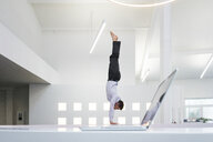 Businessman doing a handstand at laptop in office - MOEF02211