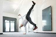 Businessman with cell phone doing a one-handed handstand on office floor - MOEF02214