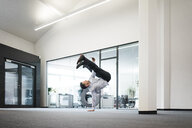 Businessman with cell phone doing a one-handed handstand on office floor - MOEF02217