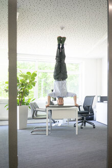 Businessman doing a headstand on desk in office - MOEF02232