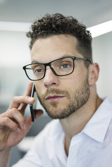 Portrait of businessman on cell phone in office - MOEF02250