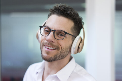 Portrait of smiling businessman listening to music with headphones - MOEF02259