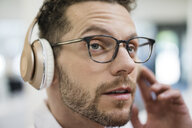 Portrait of businessman listening to music with headphones - MOEF02262