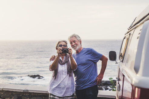 Senior couple traveling in a vintage van, taking pictures at the sea - SIPF02008