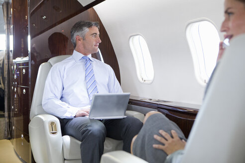 Businesswoman on phone and Businessman with digital tablet having meeting on private jet - JUIF01210