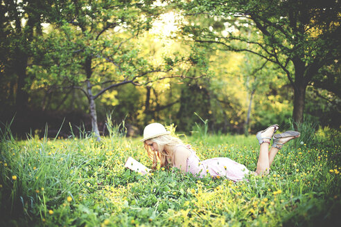Woman reading book and laying in rural field - BLEF05838