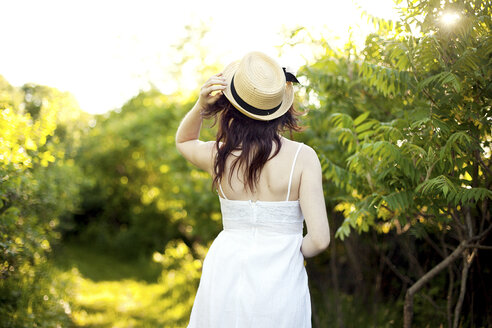 Caucasian woman holding hat on rural path - BLEF05847