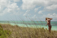 Woman in bikini standing in beach grass - BLEF06075
