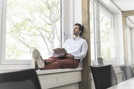 Young businessman with digital tablet sitting on windowsill, taking a break - UUF17702