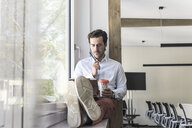 Young businessman sitting on windowsill, using digital tablet, drinking coffee - UUF17705