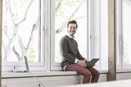 Young businessman sitting on windowsill, using laptop - UUF17711