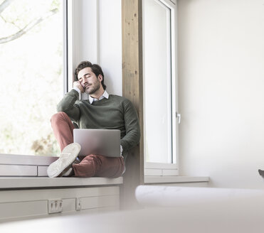 Young businessman with laptop sitting on windowsill, taking a break - UUF17714