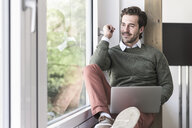 Young businessman sitting on windowsill, using laptop - UUF17717
