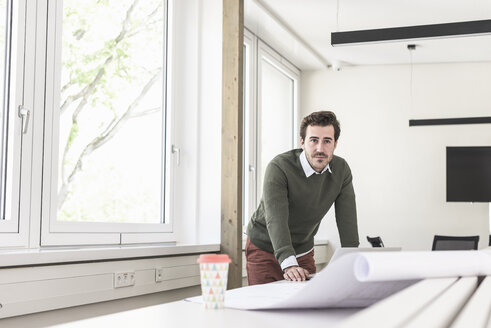 Young architect working on blueprint in bright office - UUF17720