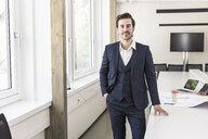 Confident businessman standing in boardroom - UUF17735