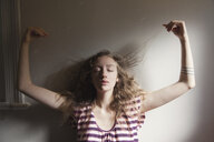 Woman playing with her hair in sunlight - BLEF06163