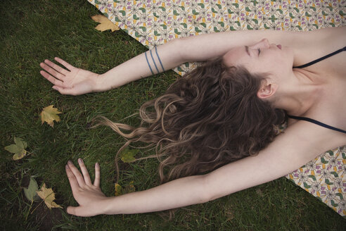 Woman laying on blanket in grass - BLEF06169