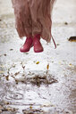 Caucasian girl in rain boots jumping in rain puddles - BLEF06175