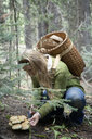Woman foraging for mushrooms in forest - BLEF06214