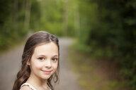 Caucasian girl smiling on dirt road - BLEF06424
