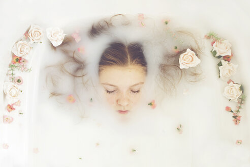 Caucasian teenage girl floating in milk bath with flowers - BLEF06478