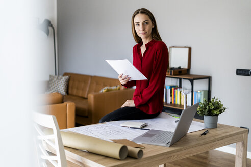 Woman in office holding paper with wind turbine model on table - GIOF06398