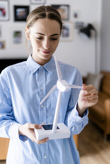 Confident woman in office holding wind turbine model - GIOF06407