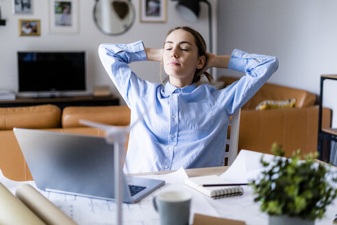 Woman in office leaning back with plan, laptop and wind turbine model on table - GIOF06434