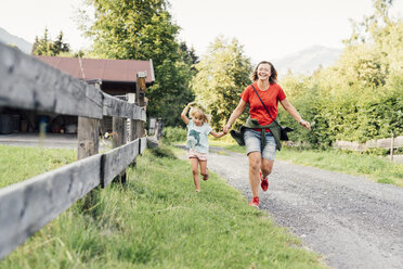 Happy mother and daughter running on a rural path, Jochberg, Austria - PSIF00277