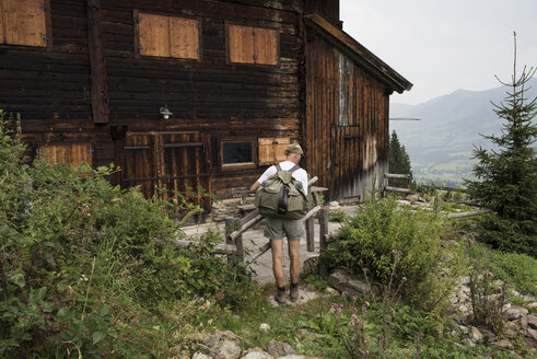 Hiker standing at wooden house, Jochberg, Austria - PSIF00280