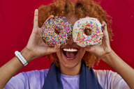 Playful woman holding two donuts in front of her eyes - VEGF00281