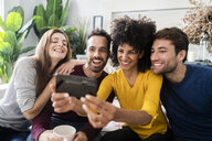 Four happy friends sitting on couch taking a selfie - GIOF06442